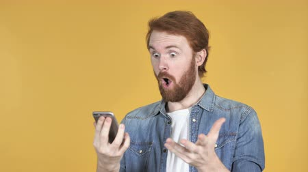 adam : Amazed Redhead Man Surprising While Using Smartphone Isolated On Yellow Background