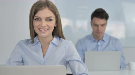 трейдер : Smiling Young Businesswoman Looking at Camera in Office