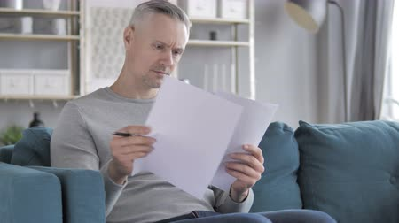 подпись : Gray Hair Man Reading Documents while Sitting on Sofa, Paperwork