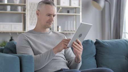 página da internet : Gray Hair Man Browsing Internet on Tablet while Sitting on Couch