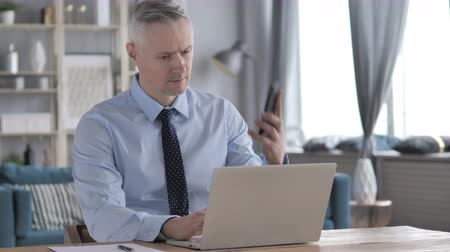 hang : Gray Hair Businessman Attending Phone Call While Working