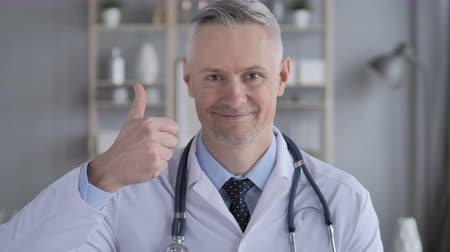 duim : Thumbs Up van Positive Doctor with Grey Hairs Stockvideo