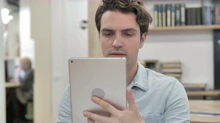 navegador : Man Browsing and Scrolling on Tablet
