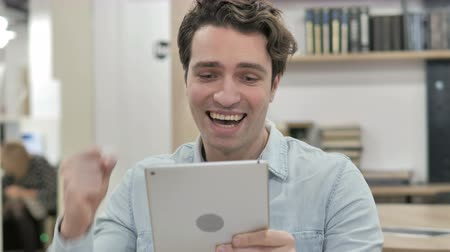 Man Celebrating Success while Using Tablet