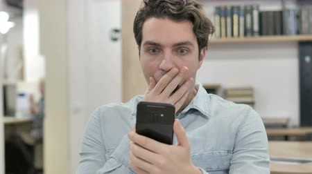 Shocked Creative Man in Awe while Using Smartphone Wideo