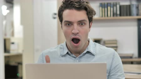 Shocked Creative Man Wondering and Working on Laptop Стоковые видеозаписи