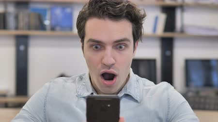 Portrait of Creative Man in Shock while Using Smartphone