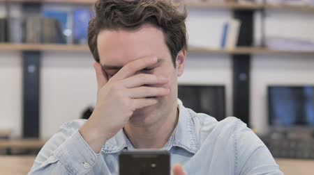 Portrait Of A Creative Man Reacting To Loss While Using Smartphone Wideo