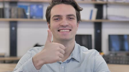 Thumbs Up by Creative Man Looking at Camera at Work Стоковые видеозаписи
