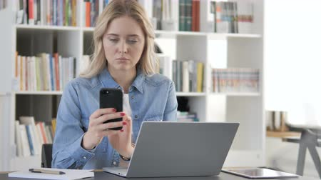 navegador : Young Woman Using Smartphone for Online Work Stock Footage