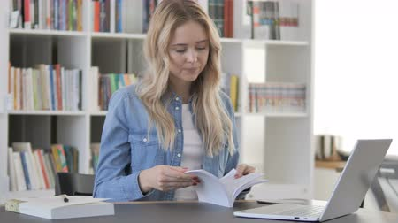 začít : Young Woman Reading Book in Library