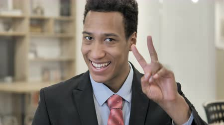 Victory Sign by Positive African Businessman