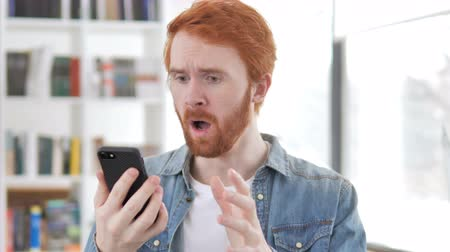 ashamed : Casual Redhead Man Reacting to Loss in Smartphone Stock Footage