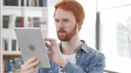 página da internet : Casual Redhead Man Browsing on Tablet