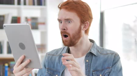 ashamed : Casual Redhead Man Reacting to Loss while Using Tablet