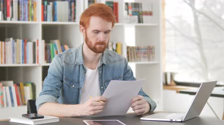 grasduinen : Casual Redhead Man Reading Documents, Contract Stockvideo