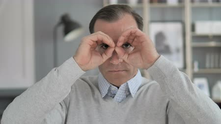 invite : Handmade Binocular Gesture by Middle Aged Man Searching New Chance