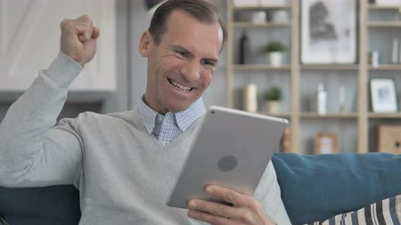 torcendo : Relaxing Middle Aged Man Celebrating Success on Tablet Vídeos
