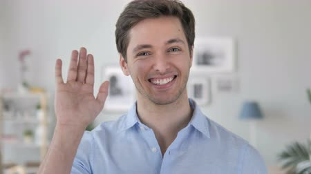 saying : Hello, Handsome Young Man Waving Hand to Welcome