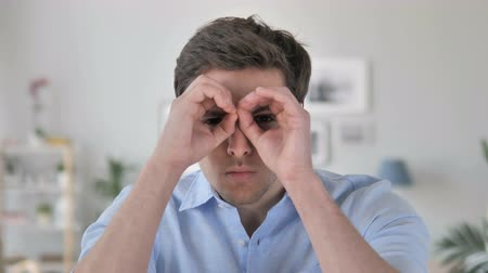 招待状 : Handmade Binocular Gesture by Handsome Young Man Searching New Chance