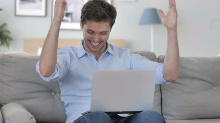 suceder : Handsome Young Man Celebrating Success on Laptop
