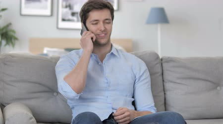 discar : Young Man Talking on Phone while Relaxing on Sofa Stock Footage