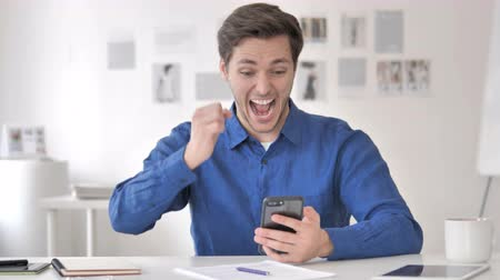 torcendo : Casual Adult Man Celebrating Success on Smartphone Vídeos