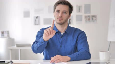 warsztat : Young Man Rejecting Offer while Sitting at Workplace Wideo