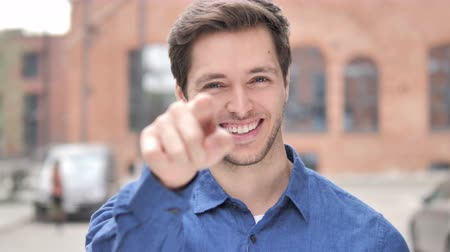 invite : Outdoor Standing Young Man Pointing with Finger toward Camera Stock Footage