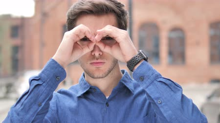 invite : Handmade Binocular Gesture by Handsome Young Man Searching New Chance