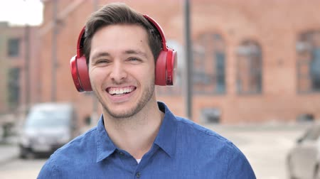 bas : Outdoor Young Man Listening Music on Red Headphones