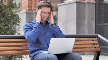 ławka : Sitting Outdoor Young Man with Headache Using Laptop