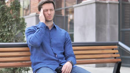 disturbed : Headache Tense Young Man Sitting Outdoor on Bench