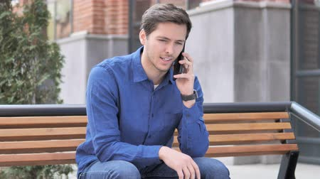 discar : Young Man Talking on Phone, Sitting Outdoor on bench Stock Footage