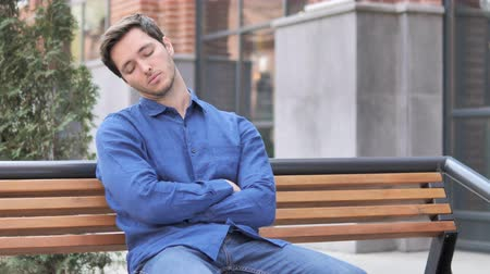 nuda : oung Man Sleeping While Sitting On Bench