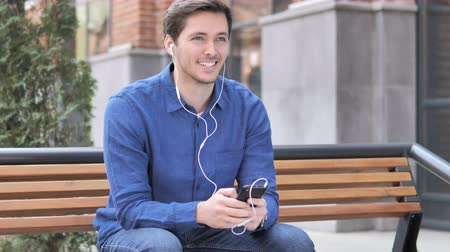 bas : Young Man Listening Music on Smartphone while Sitting on Bench