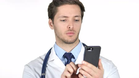 e mail address : Young Doctor Browsing Smartphone, White Background Stock Footage