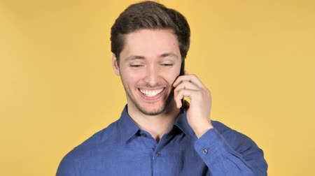 discar : Casual Young Man Talking on Phone on Yellow Background