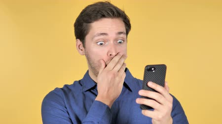 good looking guy : Wow, Surprised Casual Man Using Smartphone on Yellow Background