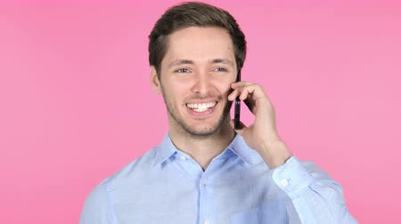 answering : Young Man Talking on Phone on Pink Background