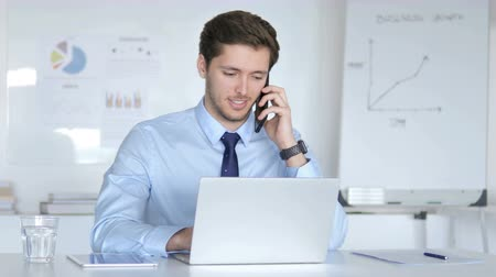discar : Young Businessman Talking on Phone at Work Stock Footage