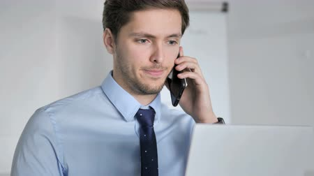 discar : Close Up of Young Businessman Talking on Phone at Work