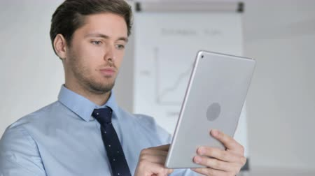 megvitatása : Close Up Of A Young Businessman Using Tablet In Office