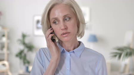 discar : Aged Woman Negotiating on Phone Stock Footage