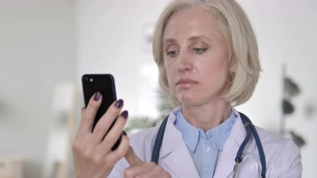discar : Senior Lady Doctor Talking on Phone Stock Footage