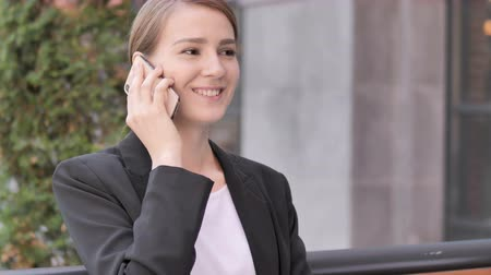 discar : Young Businesswoman Talking on Phone Sitting Outdoor Stock Footage