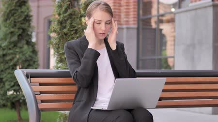 disturbed : Sitting Outdoor Young Businesswoman with Headache Using Laptop Stock Footage