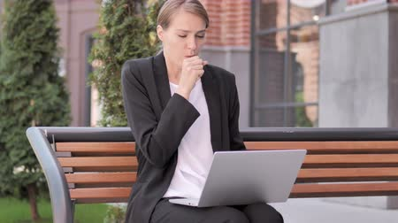 coughing : Young Businesswoman Coughing while Working on Laptop Outdoor