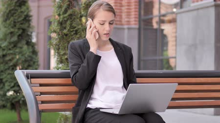 discar : Young businesswoman talking on phone sitting on bench