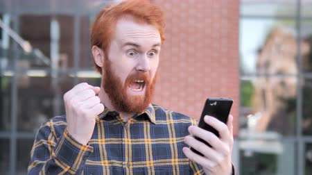 学生 : Outdoor Redhead Beard Young Man Excited for Success on Smartphone